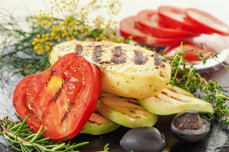 A piece of grilled halloumi cheese with fried tomatoes, courgettes and Basil. Traditional serving of halloumi cheese. Farm natural product.