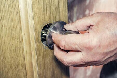 Installation of the door, the worker installs the door handle, hands carpenter closeup. Handyman installs a new door lock in the room. Replacement of broken handle. Selective focus.