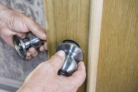 Door installation, worker installs the door handle, carpenters hands closeup. Handyman installs a new door lock in the room.