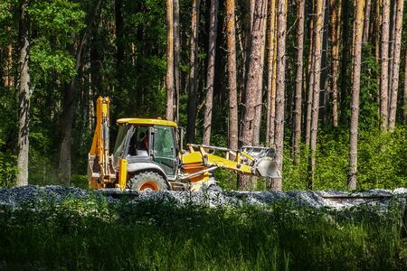 Excavator works on the construction of the railway in the forest. Yellow excavator pours the gravel between the sleepers.