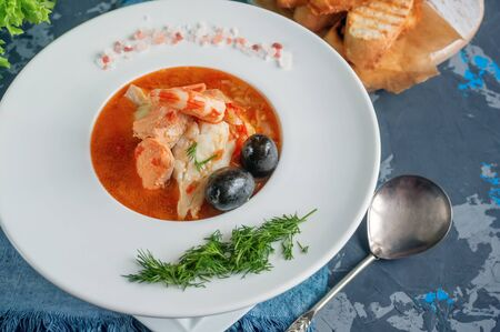 Diet soup of seafood and fish of different varieties in a white plate. Close up. Фото со стока