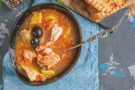 Seafood soup, salmon and cod with potatoes. Served with lemon and olives. Close up.