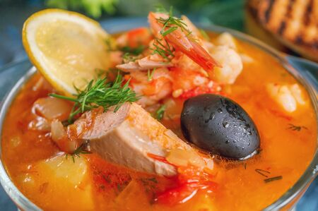 Seafood, salmon and cod soup with potatoes. Served with lemon, olives and delicious white bread croutons. Close up.