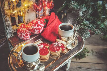 Two cups of coffee with ginger cookies in the form of red mittens on a Christmas chair next to the Christmas tree Banco de Imagens