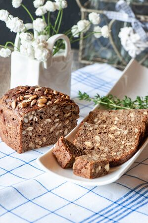 Freshly baked rye bread with seeds and raisins on sourdough without yeast on a white plate. Homemade cake. Fermentation process. Slow baking.