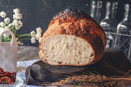 Freshly baked yeast-free sourdough wheat bread with black salt. Homemade cake.
