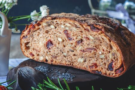 Freshly baked rye bread with seeds and raisins on sourdough without yeast with dried tomatoes rosemary and thyme. Homemade cake.