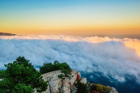 Magical sunset in the mountains above the clouds. The peak of Ai-Petri in the Crimea in the evening, when the sun sets behind the mountain.