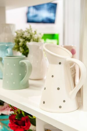A pitcher and a set of clean dishes and home furnishings on white shelves in the kitchen.