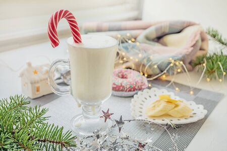 Irish traditional winter cream cocktail eggnog in a glass mug with milk, rum and cinnamon, banana covered with whipped cream, Christmas decorations. Natural smoothies. 스톡 콘텐츠