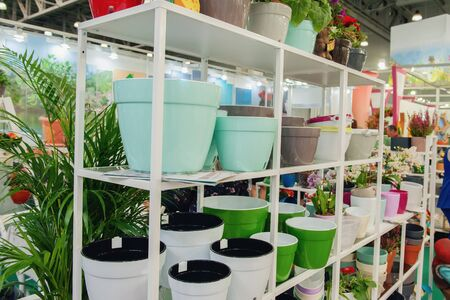 Ceramic multi-colored pots and vases for flowers on white shelves in the market.