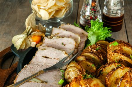 A piece of baked stuffed meat with potatoes and vegetables in a frying pan and a wooden Board.