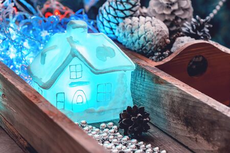 Festive Christmas decor. A luminous glass decorative transparent house lies in a box with Christmas tree needles for decorating the house and the Christmas tree. Stockfoto
