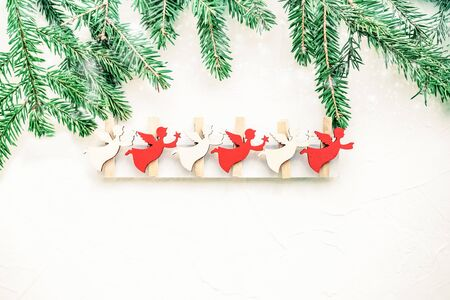 Small colored figures of angels with Christmas tree branches on a light background with shiny snowflakes. Snowfall. Copy space. Stock Photo