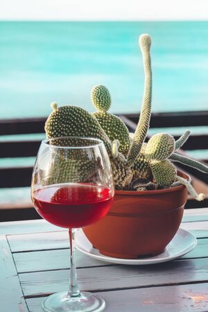 A glass of dry red wine sits on a wooden table next to a cactus against the sea. The concept of rest. Stock Photo