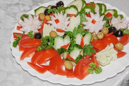 Vegetable salad with juicy tomatoes, radishes, lettuce, green olives, cucumber, red onion and fresh parsley. Homemade food. Symbolic image. The concept of delicious and healthy vegetarian food. Close up. Фото со стока