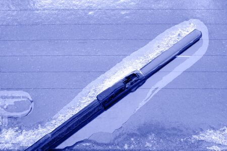 Detail of the ice car body and brush to clean the window after an icy rain. Unprotected open transport in winter weather conditions. Tobed, copy space