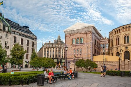 Oslo, Norway-August 1, 2013: Stortinget Parliament building Oslo Norway with beautiful fine light clouds. People rest on the square in front of the Parliament. Editorial