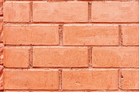 A fragment of a red brick wall in close-up. Background for the designer.