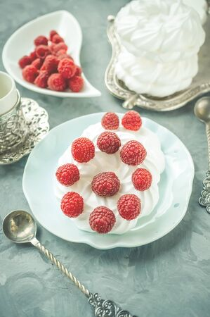 Delicious mini Pavlova meringue cake decorated with fresh raspberries, with a beautiful Cup lying on a platter.