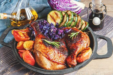 Fried pickled duck legs with a side dish of vegetables . Grilled zucchini, red cabbage and spices on a wooden table.