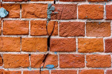 An old weathered fragment of a brick wall with cracks. Background for the designer. A large brick.