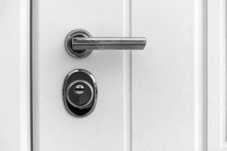 detail of a closed door with a lock handle and a white background. Metal handle and lock on the front door.