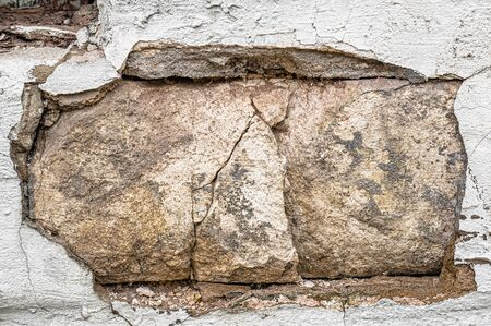 gray cement wall with deep cracks from age and precipitation. Old cracked plaster. A fragment of a concrete wall.