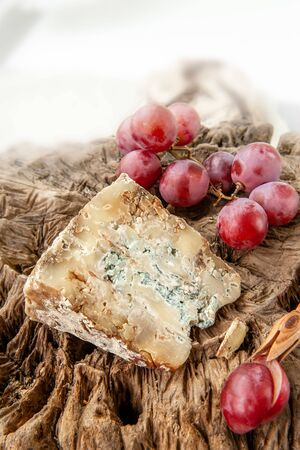 A piece of blue Stilton cheese on a wooden antique with large red grapes.