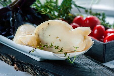 Fresh, traditional Italian cow or goat and sheep cheese semi-sweet Caciocavallo, Scamorza with aromatic herbs in the cut.