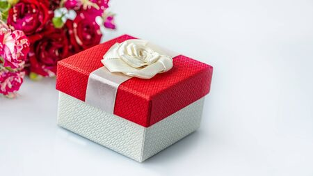 Red gift box and a bouquet of roses on a white background with a copy of the space.