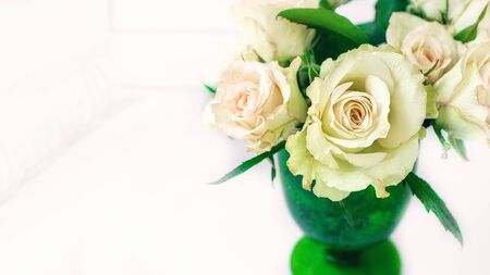 Romantic bouquet of delicate greenish roses in a green glass of thick glass on a light background. Close-up, copy space.