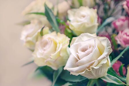 Romantic bouquet of delicate greenish roses on a light background. Close-up, copy space.