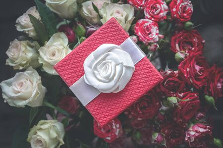 Red gift box and a bouquet of roses top view. Archivio Fotografico
