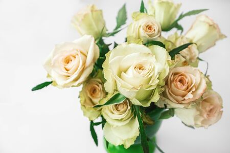 Romantic bouquet of delicate greenish roses on a light background. Background of cream and pink roses. Close-up, selective focus.