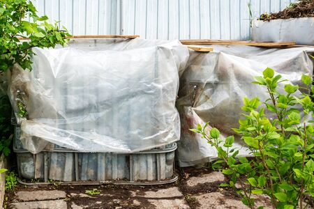 Plastic containers are reused for composting waste in the garden. fresh composted earth from the compost bin. Cover the compost from rain and waterlogging. Archivio Fotografico