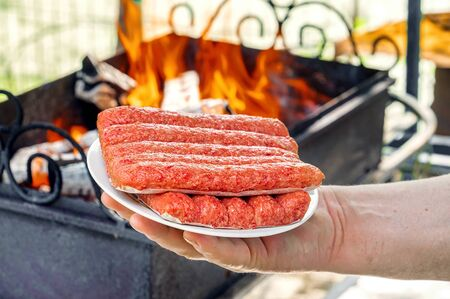 Chevapchichi on a plate in your hand. A man holds fresh chevapchichi on a white platter against the background of a barbecue fire. Grilled chevapchichi is a Balkan national dish.