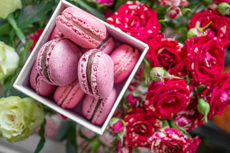 Delicate raspberry macaroons on the table with a bouquet of scarlet and white roses. Close up. Selective focus.