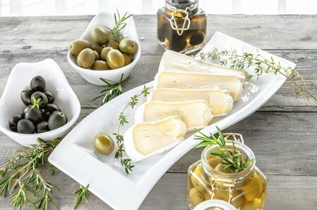 Olives are green and black with soft cheese with mold like brie, Camembert with olive oil and thyme.