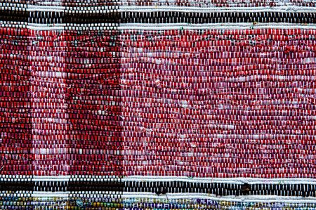 Colorful woven cotton thread rug fabric. A fragment of handmade fabric in red.