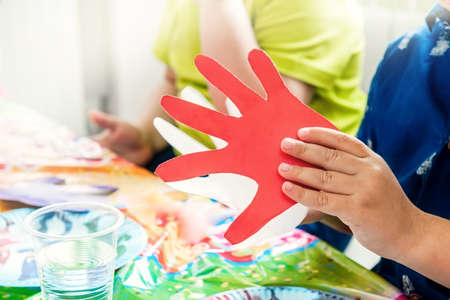 child's hands play with a cardboard red palm. Children's classes in the kindergarten. Educational classes for children.