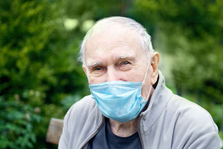 old man in a medical mask in the open air, so as not to get infected with the virus, smiles. Prevention of viral diseases. Loneliness of old people