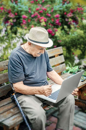 elderly man in a straw hat is working on a laptop and enjoying life, smiling happily. An old man with a mustache gestures that everything is in order Stock Photo