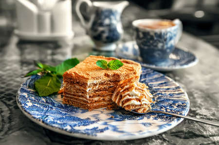 Layered piece of honey cake on an antique plate. Close-up of a delicious honey cake with mint Archivio Fotografico