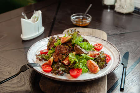 warm chicken liver salad with figs is served on a white plate with a sauce of French mustard and honey. Close up
