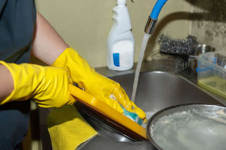 washing dishes under running water close-up. Womens hands in yellow household gloves clean dishes before washing in the dishwasher Archivio Fotografico