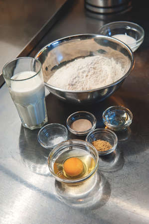 Baking a cake in a rural kitchen - a recipe for a dough with the ingredients eggs, flour, milk, butter, sugar and yeast on the table. Ingredients for making the dough Archivio Fotografico