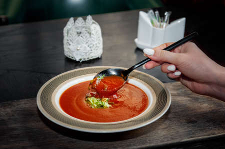 Gazpacho diet tomato soup with herbs and cucumber on a plate. A womans hand with a spoon of soup. Close up