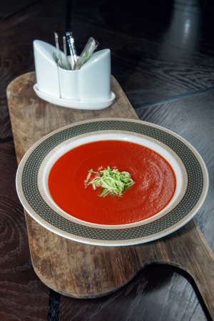 Gazpacho diet tomato soup with herbs and cucumber on a plate