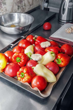 vegetables are ready for cooking. Garlic, pepper and tomatoes are on a baking sheet. Cooking healthy food dishes from vegetables Archivio Fotografico